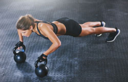 Girl with dumbbells pressed on the floor